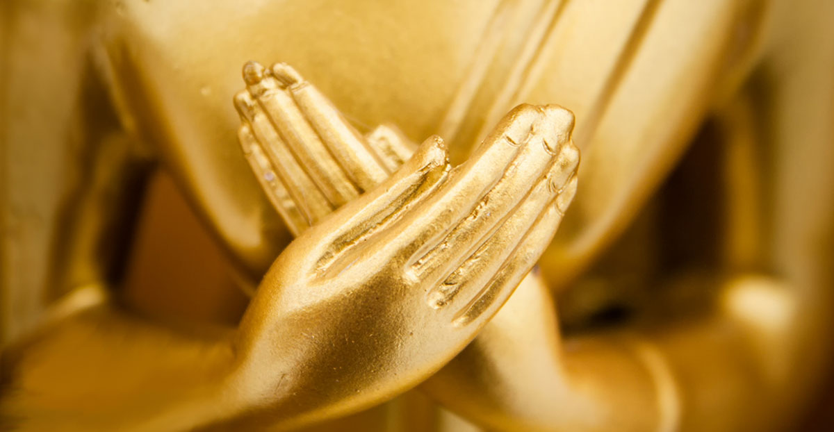 Buddha statue with hands over heart